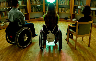 Two people in wheelchairs and one in a chair in front of a TV in the library