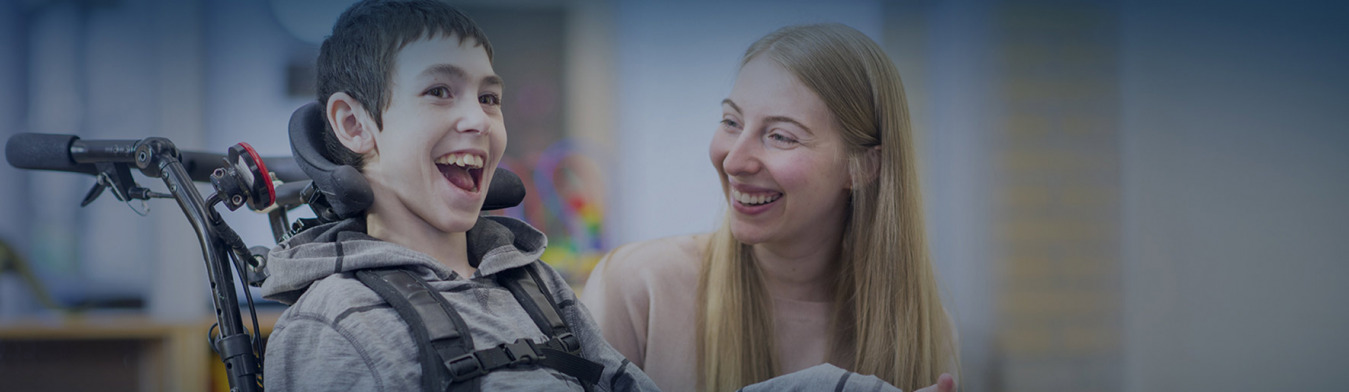 kid with disability smiling with a woman