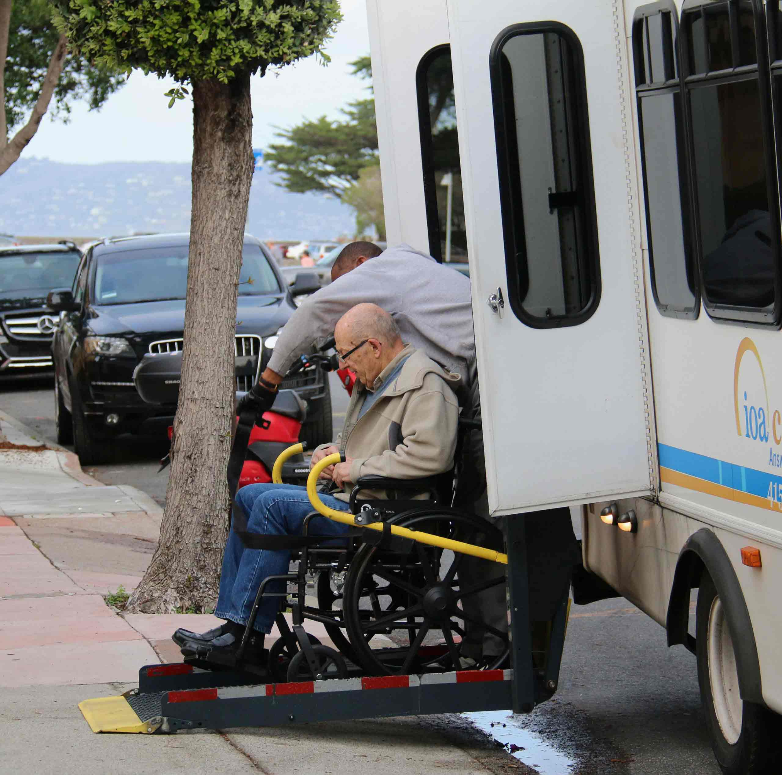 Man in a wheelchair is assisted to get off a van using a lift in San Francisco
