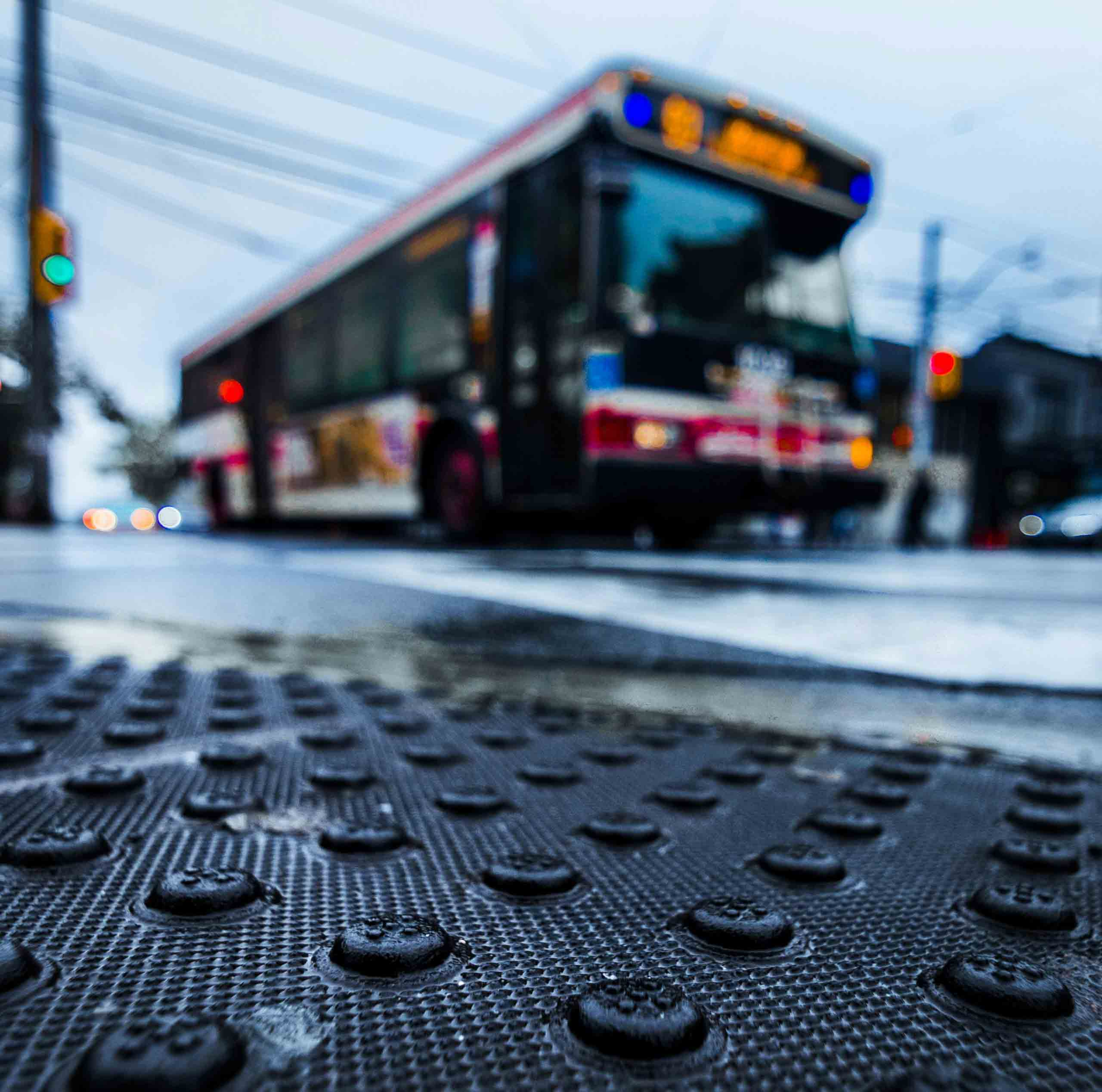 Low angle shot of Toronto transit bus driving past street corner with lots of texture from tactile walking surface indicators.