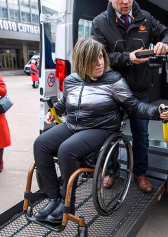 a woman in wheelchair getting off from an accessible taxi