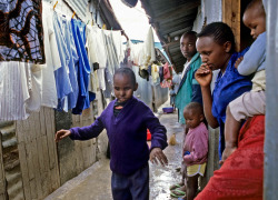 a blind boy to walk alone in a narrow corridor between the shacks, hovels, houses of corrugated iron or wood, slum, Nairobi