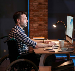 Side view of disabled businessman working in office