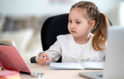 girl, doing homework, writing in notebook, using laptop