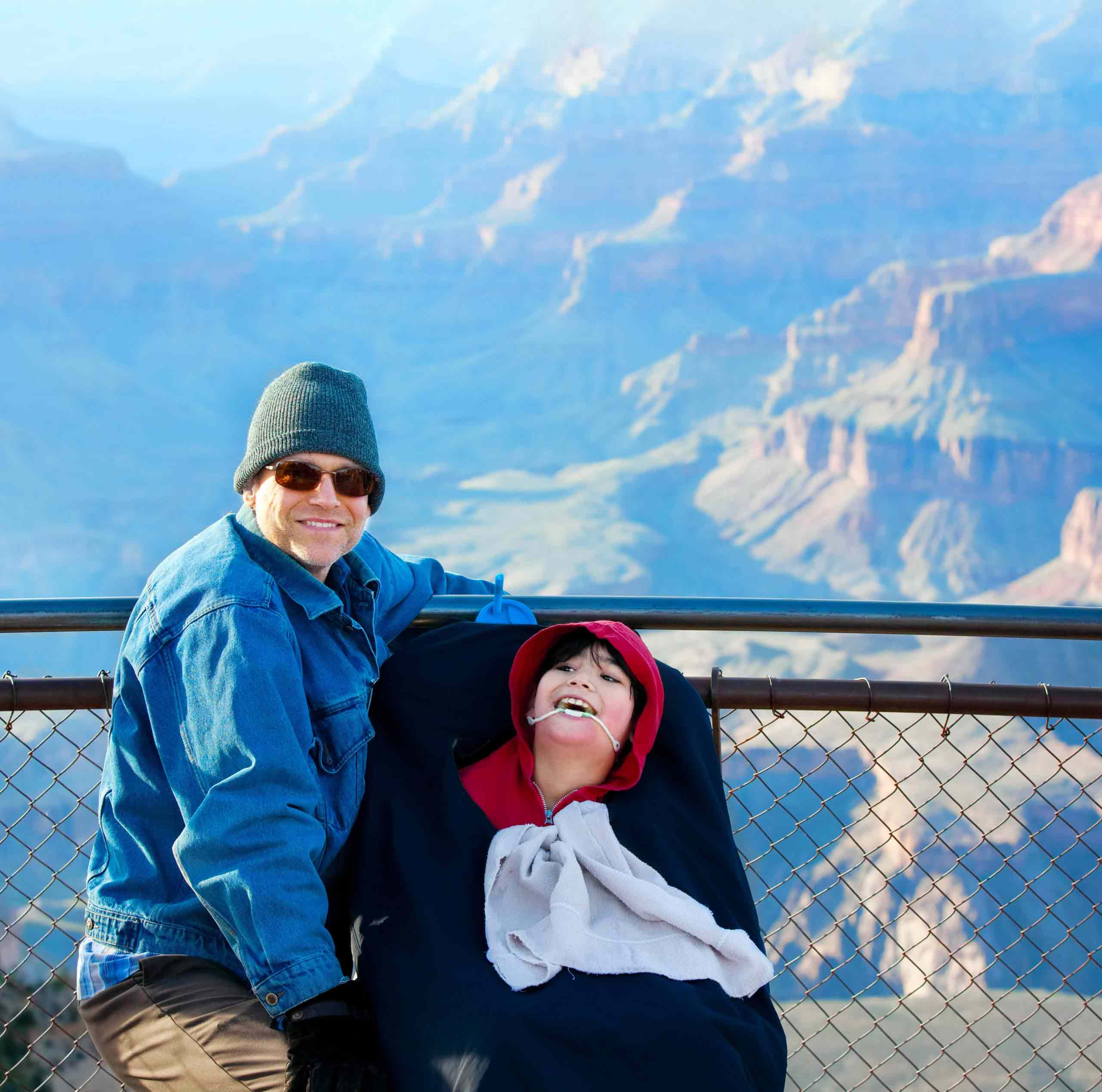 Father sitting next to disabled son in wheelchair, background mountains