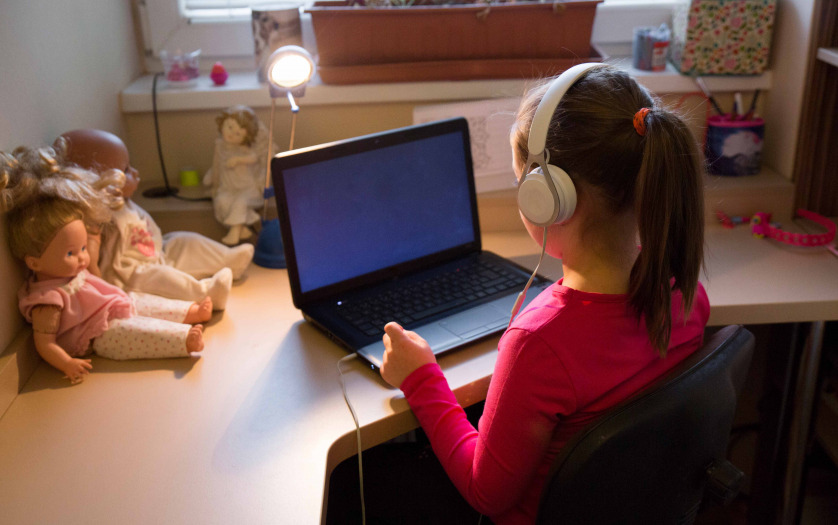 Girl in headphones using laptop