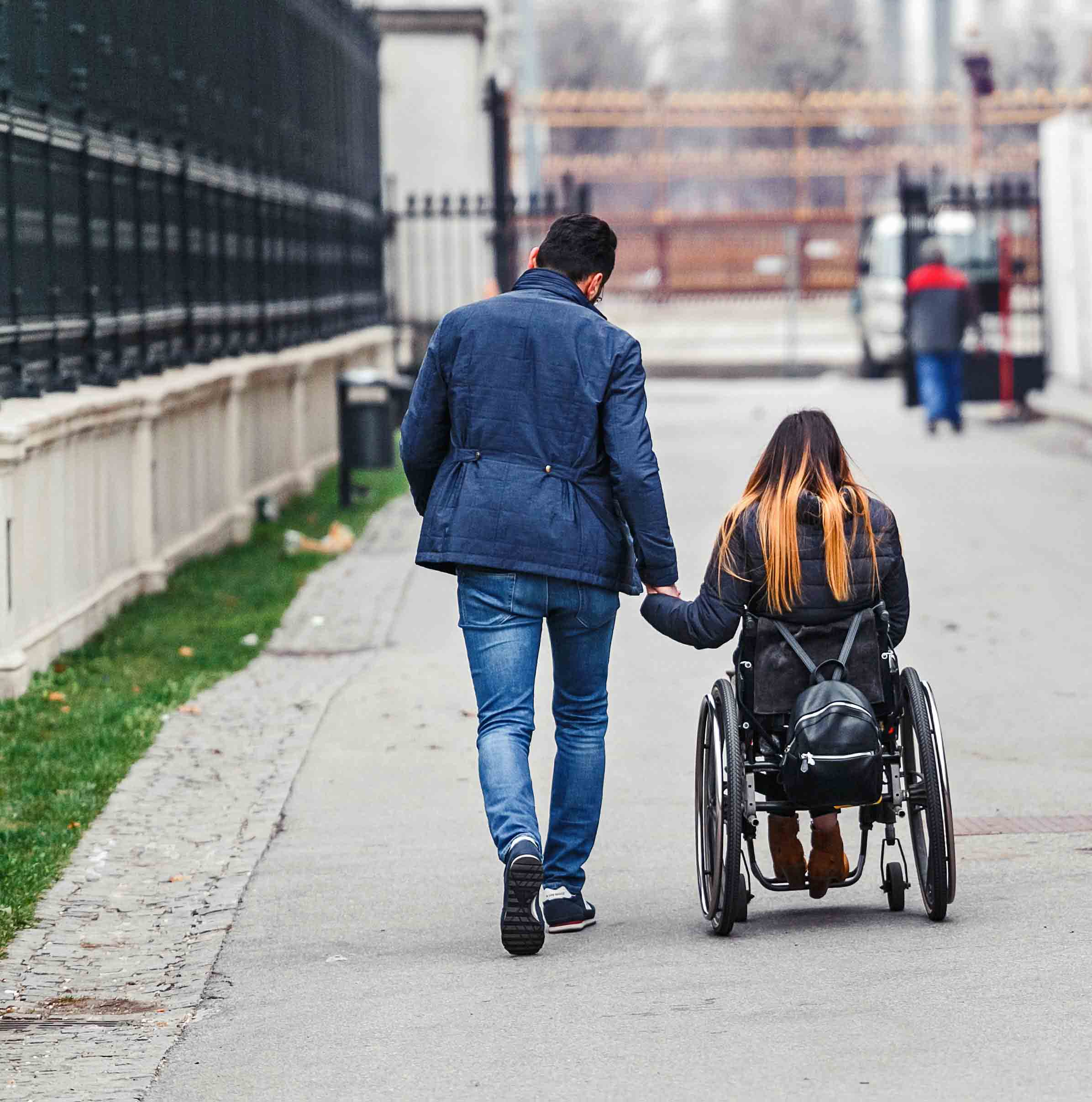 A man with his beloved girlfriend in wheelchair is traveling around the city of Vienna in Austria