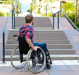 student in wheelchair in front of stairs