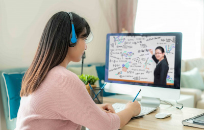 Asian woman student video conference e-learning with teacher on computer in living room at home