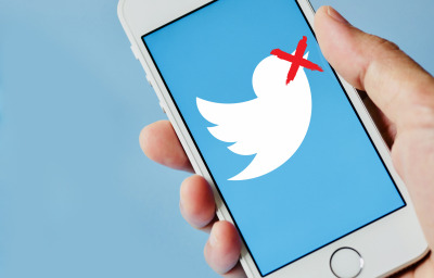 person holding smartphone with twitter screen with red cross on twitter icon
