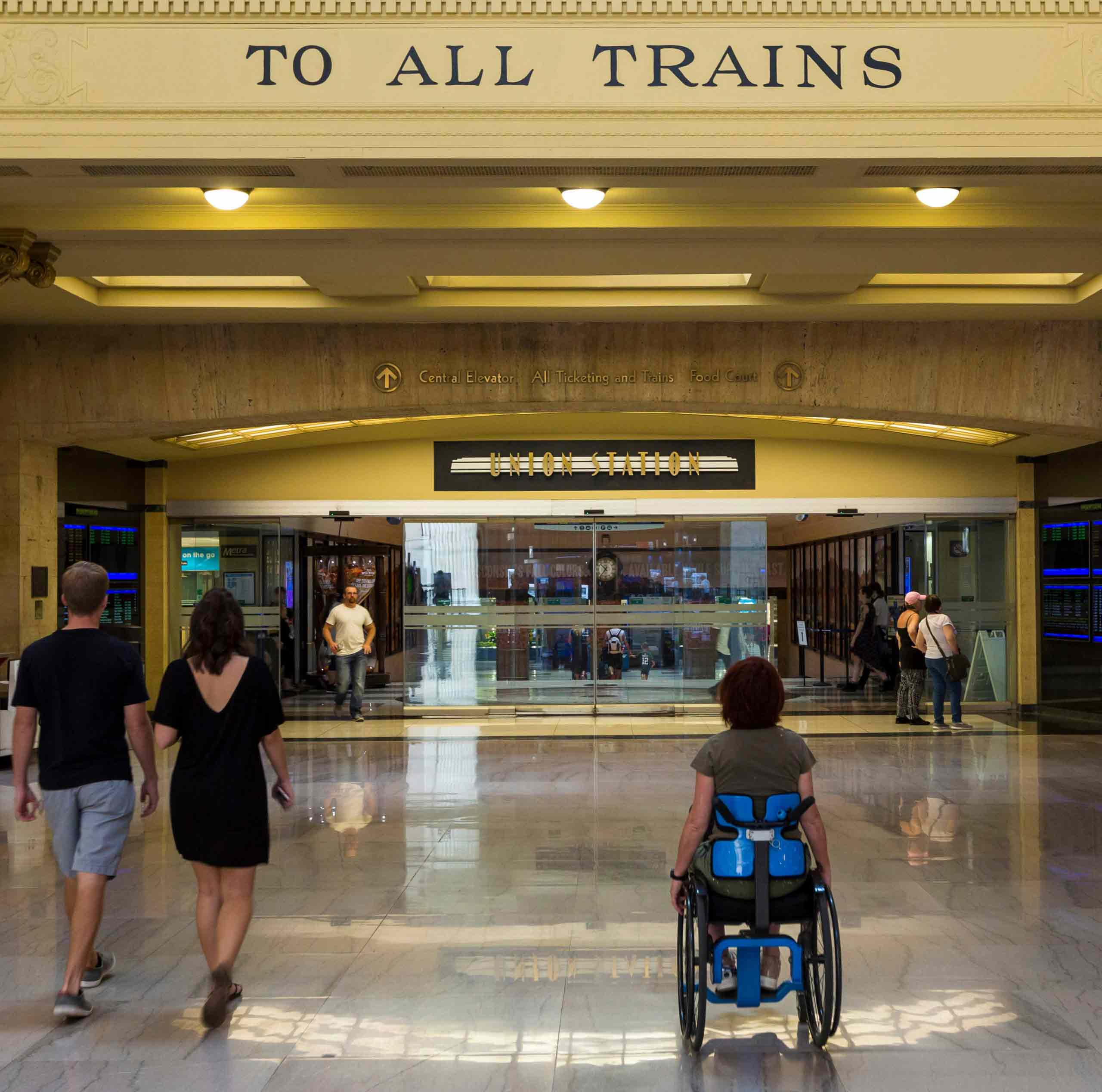 woman in wheelchair entering the station