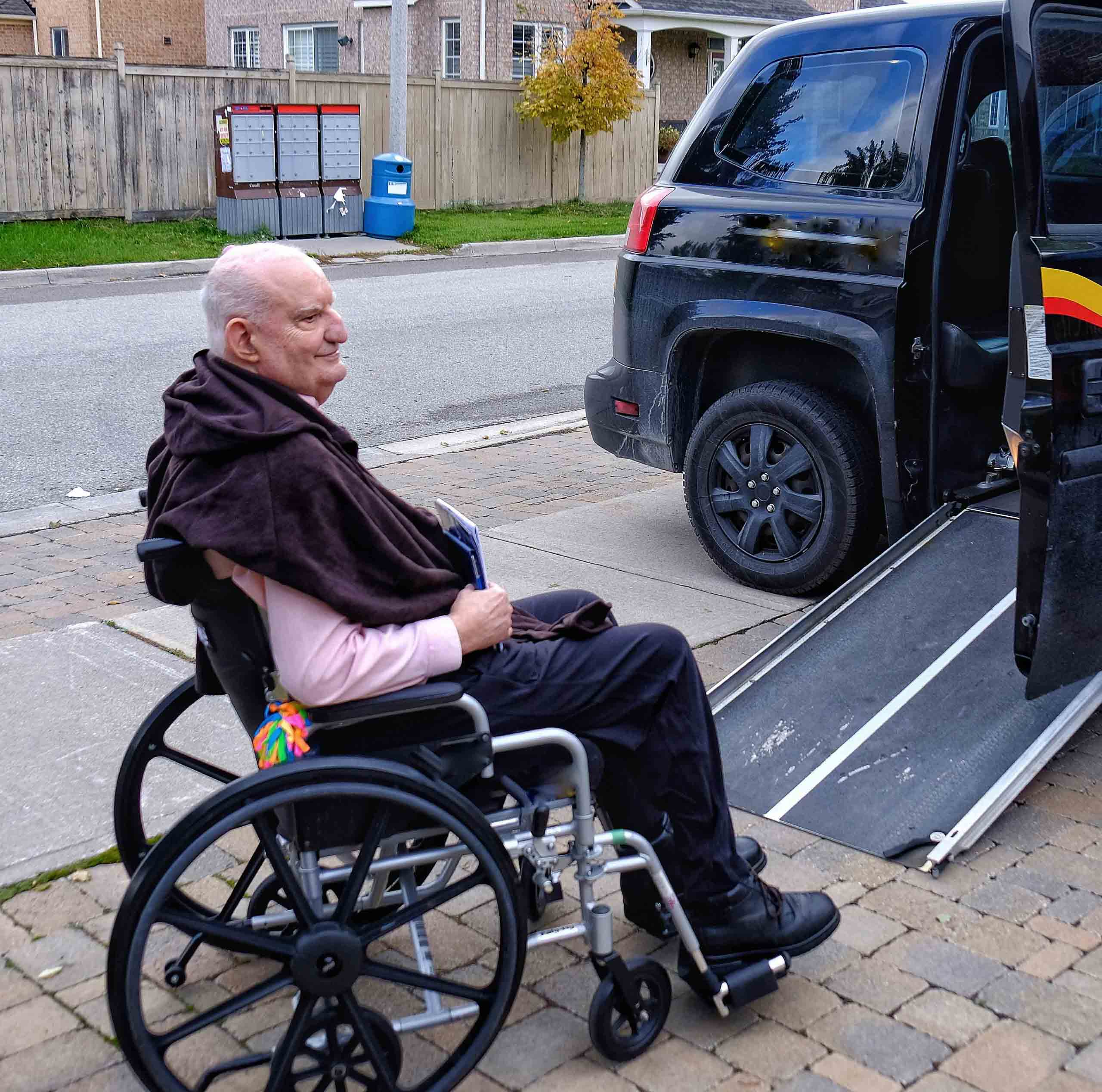 Man in wheelchair waiting to go up ramp into wheelchair cab