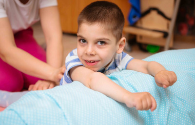 kid with cerebral palsy has musculoskeletal therapy by doing exercises