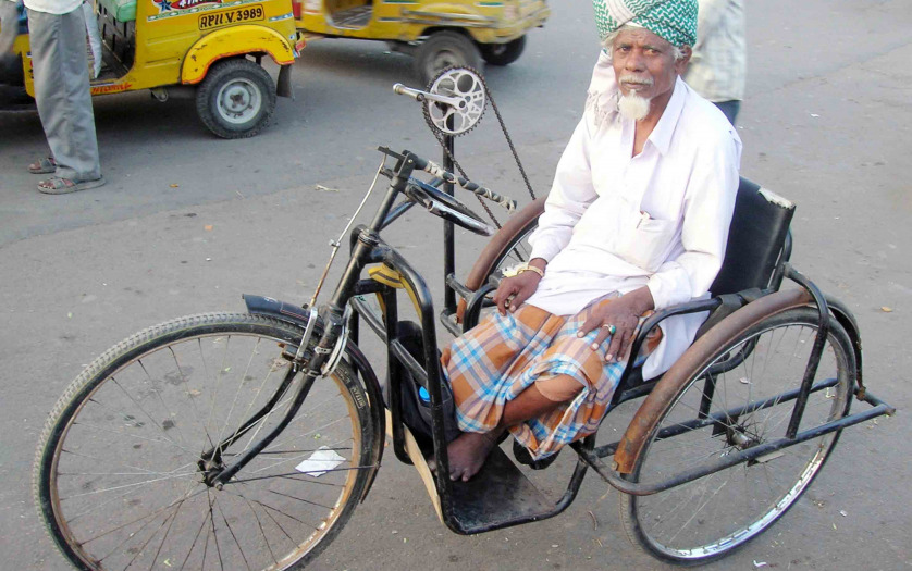 Man with a disability using a tricycle on road, Hyderabad