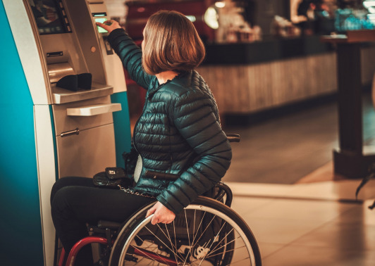 woman in wheelchair using ATM