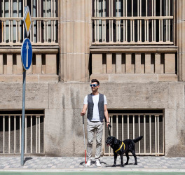 Young blind man with white cane and guide dog standing on pavement in city
