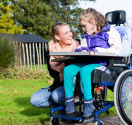 Child in a wheelchair relaxing outside with a care assistant