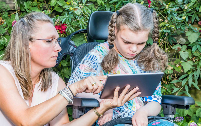 A child in a wheelchair sitting outside looking at a tablet together with a care worker