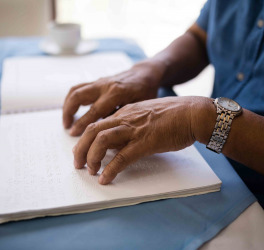 man reading braille book at table