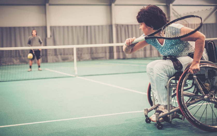 woman on wheelchair playing tennis on tennis court.