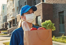 Close up portrait young courier woman holding food craft bag. Modern safety food delivery service. A delivery woman wearing medical mask.