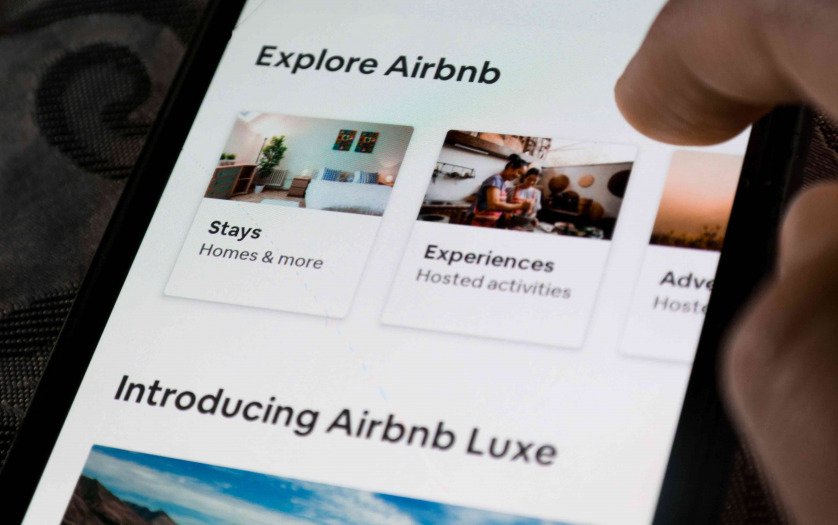 A user using the Airbnb app on a smartphone - exploring travel destinations