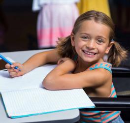Little girl in wheelchair in classroom