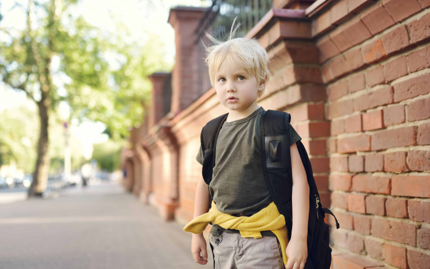 stressed little boy with backpack
