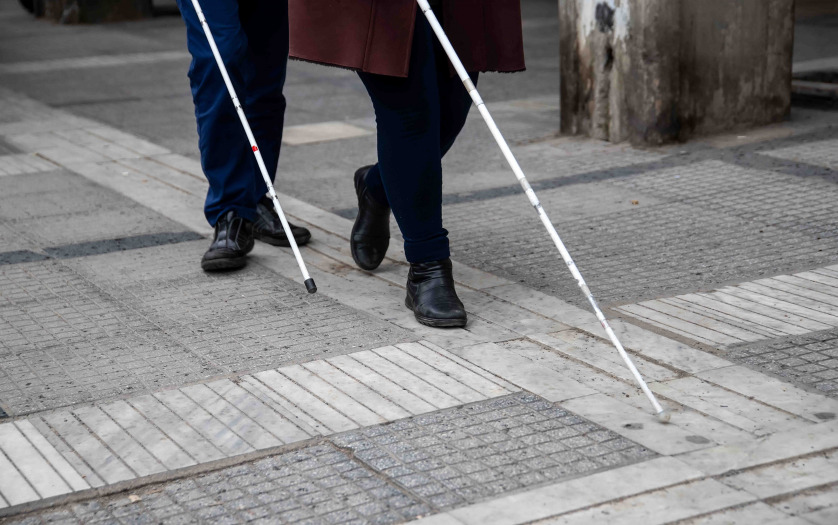 Blind man and woman walking on the street using a white walking stick