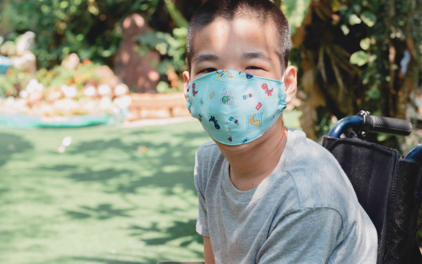 child in wheelchair wearing a protection mask