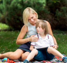 Cheerful loving mother hugging her son with disability sitting on a rug on a lawn
