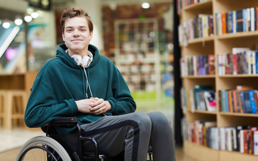 student in wheelchair in library