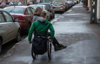 a man in a wheelchair with girl on the street