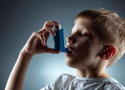 Portrait of a boy using an asthma inhaler