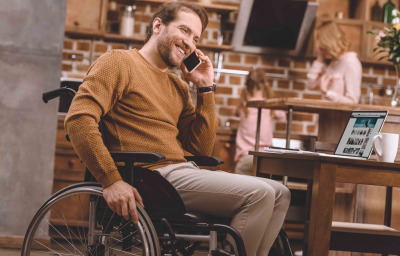 man in wheelchair talking on smartphone and using laptop