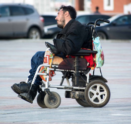 Man in electric wheelchair moving along the city street