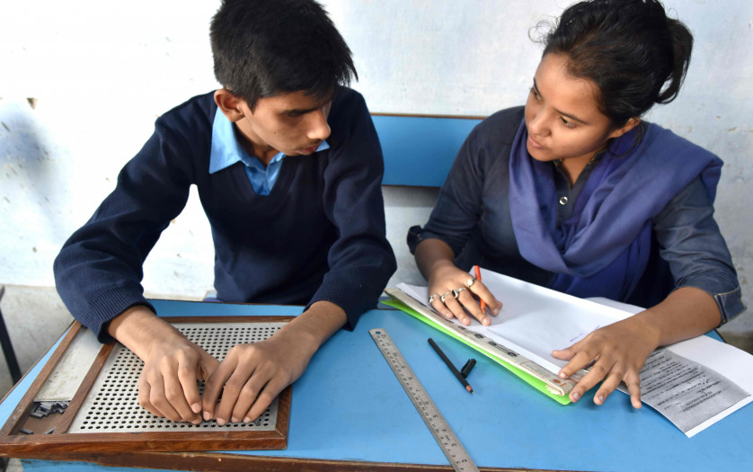 A blind Indian student giving examination to the teacher in a class room
