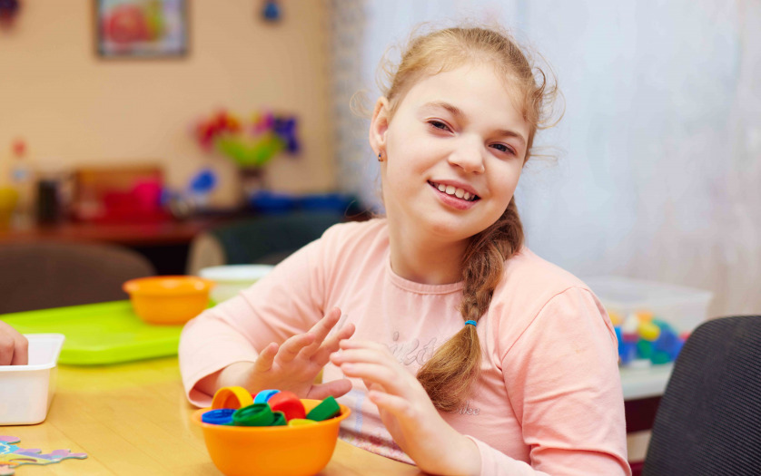 girl with disability develops the fine motor skills at rehabilitation center