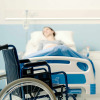 Hospitalized patient lying in bed and wheelchair in the foreground