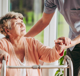 Older disabled woman trying to stand up with help of caregiver