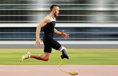 athlete amputee leg running with prosthetic on background of motion blur