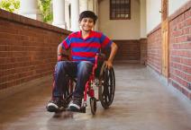 Boy sitting in wheelchair in school corridor