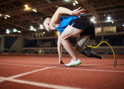 Young man with artificial leg leaning over race track while standing by start line and waiting for signal to go