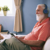 Side view of smiling senior man watching movie on tablet pc at home using wireless headphones