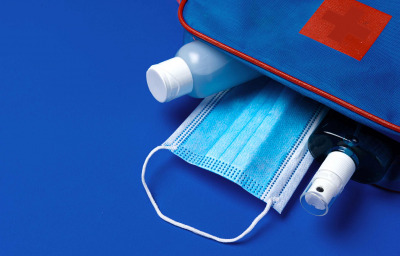 First aid kit with mask and sanitizer on blue background