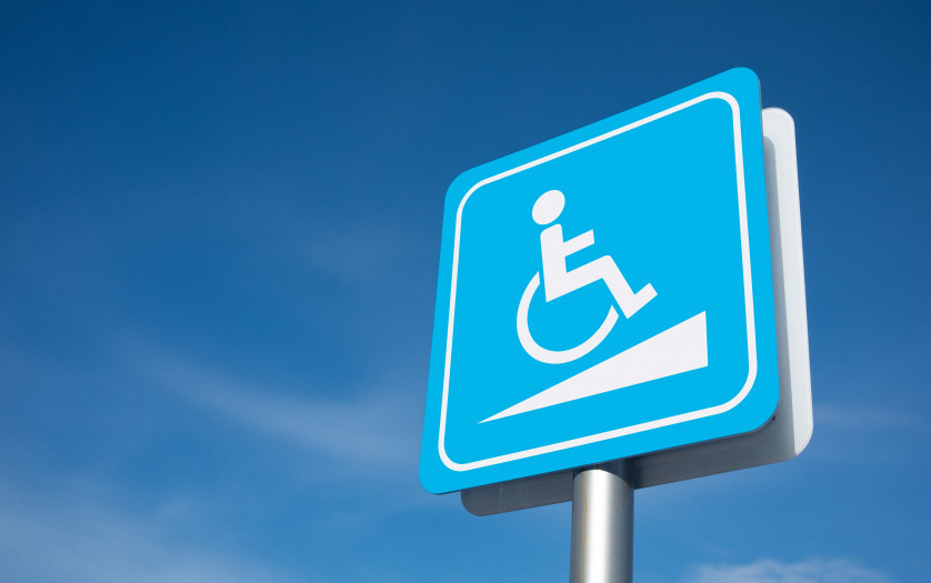 Disabled parking signage with blue sky