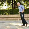 Man strolls in park with crutches, during a therapy