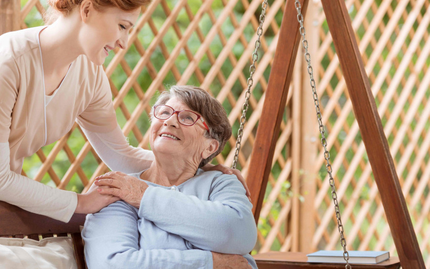 An elderly female sitting on a patio swing, Professional caretaker standing next to the woman.