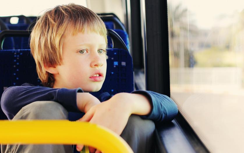 autistic boy sitting in empty bus
