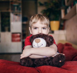 Little boy hugging his teddy bear with sad feelings